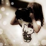 Аватар Девочка в футболке с Hello Kitty держит в руках фотоаппарат