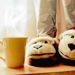 Аватар Девушка в домашних тапочках-обезьянах стоит возле кружки  с горячим напитком