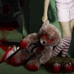 Аватар Девочка держит за ухо плюшевого медведя измазанного в крови со светящимися красными глазами и ножом в лапе