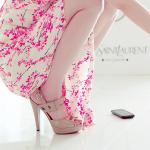 Аватар Девушка в платье с принтом в виде цветущей сакуры и туфлях на каблуке присела на корточки рядом со смартфоном
