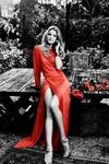 Аватар Красивая девушка в красном платье сидит на деревянном столе. Рядом лежат красные розы