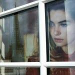 Аватар Девушка стоит у окна и смотрит на городскую улицу