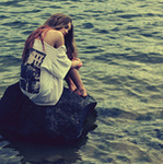 Аватар Грустная девушка в майке сидит на камне