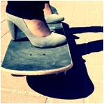 Аватар Девушка в туфлях на высоком каблуке стоит на скейте