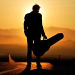 Аватар Силуэт мужчины с футляром для гитары на фоне заходящего солнца