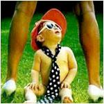Аватар Ребенок в красной кепке, черном в белую горошину галстуке сидит на траве между женских ног