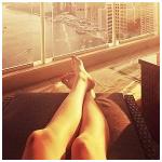 Аватар Девушка вытянула ноги на кресле, смотря на вид города в окно