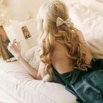 Аватар Девушка блондинка с бантиком на волосах, лежит на кровати читая книгу
