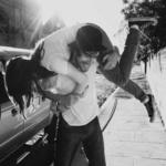 Аватар Парень поднял свою девушку на плечи, на заднем плане здание и автомобиль, припаркованный к обочине