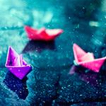 Аватар Бумажные кораблики фиолетового, красного и розового цвета лежат в луже при этом идет дождь