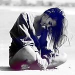 Аватар Улыбающаяся девушка опустив голову и поджав под себя ноги сидит на песке