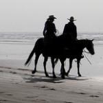 Аватар Силуэты мужчины и девушки на лошадях, прогуливающихся по побережью