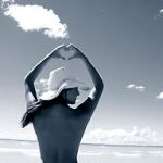 Аватар Девушка в шляпе стоит с поднятыми руками на фоне моря и неба