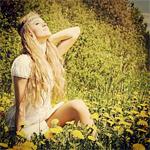 Аватар Девушка в окружении цветов и зелени, смотрит в высь