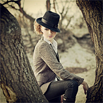 Аватар Девушка в шляпе, сидит между деревьями