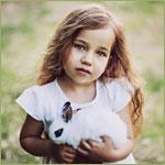 Аватар Маленькая длинноволосая девочка держит в руках белого с черным кролика