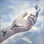 Аватар Женская рука с татуировками в виде голубей, которые оживают, на фоне облачного неба
