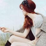 Аватар Рыжеволосая девушка, с черным украшение в волосах, с пальто на плечах, сидит и смотрит на море в профиль
