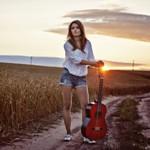 Аватар Девушка с гитарой стоит на дороге в поле на фоне заката