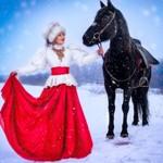 Аватар Девушка в красном платье, белой шубе и меховой шапке ведет воронного коня под уздцы по заснеженной дороге