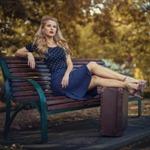 Аватар Девушка сидит на скамье в парке, положив ноги на чемодан