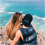 Аватар Девушка целует парня в щеку, сидя на краю горы у моря