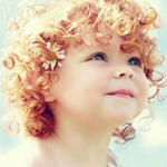 Аватар Кучерявый малыш с цветами на волосах