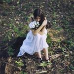 Аватар Грустная девушка с букетом цветов сидит на земле
