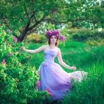 Аватар Девушка в венке стоит у куста цветов