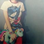 Аватар Девушка в майке с Бэтгерл / Batgirl держа в руке игрушечную пони стоит у стены