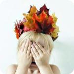 Аватар Ребенок с венком из осенних листьев на голове закрывает лицо руками