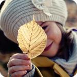 Аватар Девочка в белой шапке держит в руке желтый осенний лист
