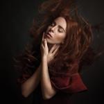 Аватар Рыжеволосая девушка с закрытыми глазами с развивающимися волосами прикасается к своему лицу руками на темном фоне
