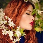 Аватар Девушка с рыжими волосами стоит у весенней цветущей ветки