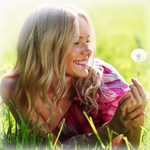 Аватар Улыбающаяся девушка лежит на траве и смотрит на одуванчик