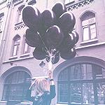 Аватар Девушка держит черные воздушные шарики в руке, стоя на улице города