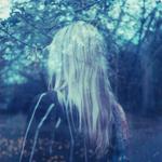 Аватар Призрачная девушка со светлыми волосами стоит спиной к зрителю на размытом фоне цветущего сада в предрассветных сумерках