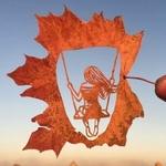 Аватар Пальцы держат осенний кленовый лист с вырезанным внутри силуэтом девушки на качели, на фоне неба