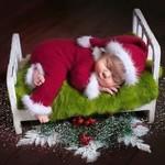 Аватар Мальчик в костюме Санта Клауса спит на кроватке