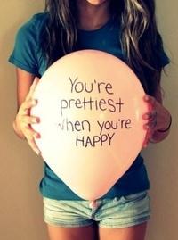 Обои Девушка держит шар с надписью You're prettiest when you're HAPPY