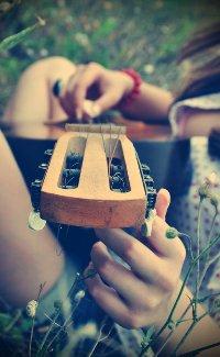 Обои Девушка играет на гитаре сидя в траве