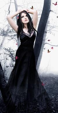 Обои Девушка в черном стоит с  поднятыми руками среди деревьев