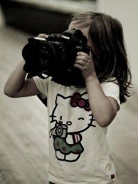 Аватар вконтакте Девушка в футболке с Hello Kitty держит в руках фотоаппарат