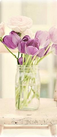 Обои Сиреневые тюльпаны и розовые розы в прозрачной вазе стоят на стуле