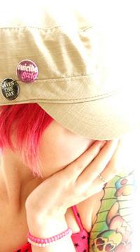Аватар вконтакте Девушка с розовыми волосами и цветными татуировками на плече, в бежевой кепке, с прикрепленными к ней значками, чёрным и розовым, с надвинутым на глаза козырьком, приложила руку к лицу