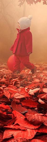 Аватар вконтакте Маленькая девочка в белой шапке с помпоном, одетая в красное пальто, шагает по осенним листьям, держа в руке красный резиновый шарик
