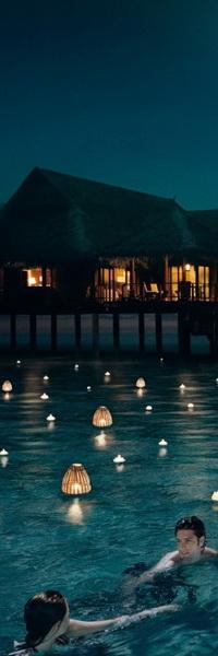 Аватар вконтакте Романтическое свидание мужчины и женщины в прибрежной океанской воде среди плавающих, горящих японских фонариков, рядом с бунгало, где они проживают, на фоне ночного неба