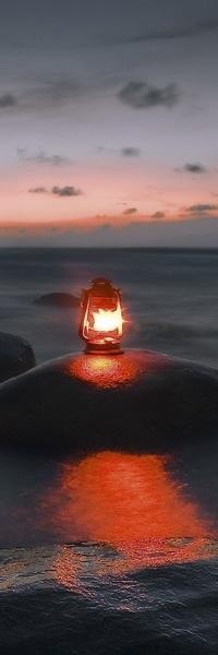 Аватар вконтакте Зажженный фонарь, светящийся красным светом, расположенный на каменном валуне в прибрежной морской воде на фоне заката, небольших темных туч на вечернем небе