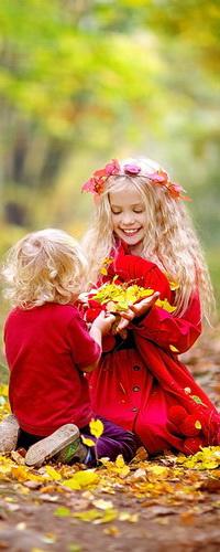 Аватар вконтакте Белокурые брат и сестра, одетые в красную одежду, сидят на коленях на лесной дорожке, усыпанной осенними листьями, и смотрят на охапку желтой листвы в руках у улыбающейся девочки с венком из оранжевых листьев на голове, автор Светлана Квашнина