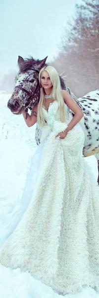 Аватар вконтакте Стройная девушка блондинка, одетая в длинное белое платье, держит под уздцы белого в яблоках коня, стоя на снегу на опушке леса, автор Светлана Беляева